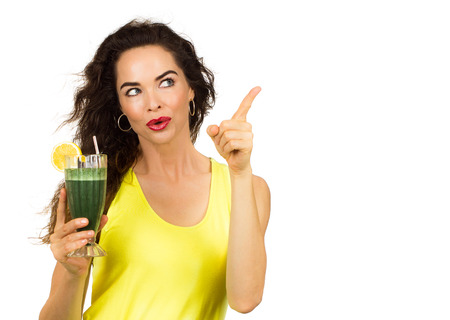 Beautiful healthy woman holding an organic green smoothie and pointing at copy-space   Isolated on white  photo