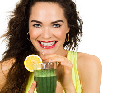 Beautiful healthy smiling woman holding and about to drink an organic green smoothie  Isolated on white  photo