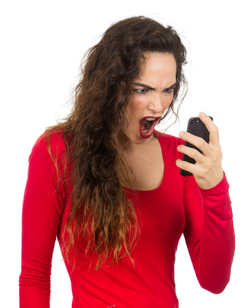 A very angry, annoyed and frustrated woman screaming at her phone in rage  Isolated on white  photo
