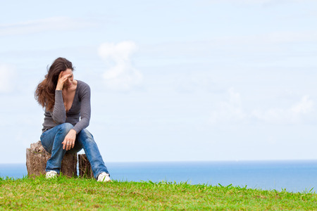 Photo of a depressed and upset young woman sitting outside with her head in her hands Stock Photo - 26901159