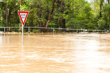 flood water: Very flooded road and give way sign in Queensland, Australia