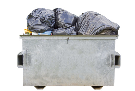 An overfull dumpster bin isolated over white photo