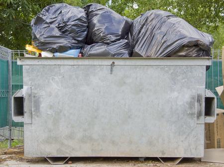 An overfull dumpster bin