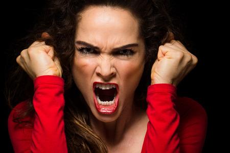 非常に怒っている積極的な女性が怒りで、彼女の拳を握り締めています。 写真素材