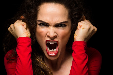 angry woman: A very angry aggressive woman is clenching her fists in rage