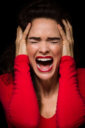 A strong dark image of a very upset, angry and emotional woman screaming  Stock Photo