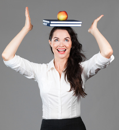 A happy beautiful business woman balancing books and an apple on her head Stock Photo