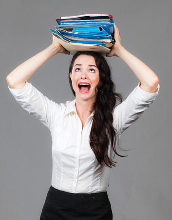 Portrait of an over worked business woman with a big pile of folders on her head Stock Photo - 26901010