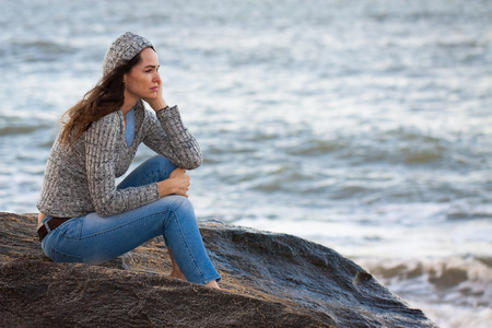 Sad and thoughtful woman sitting by the water deep in thought  Stock Photo