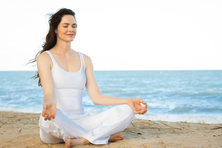 Peaceful healthy   fit young woman meditating on the beach