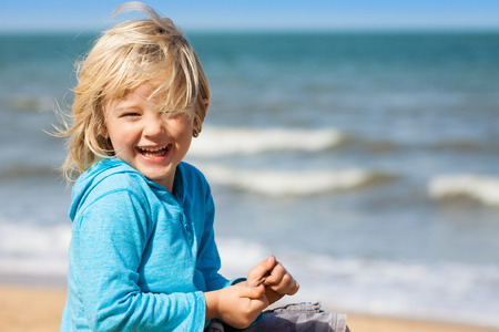 Portrait of a very cute happy boy laughing at camera at the beach