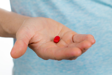 Close-up shot of a hand holding a red pill.