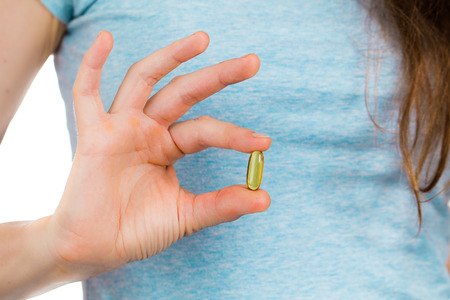 A womans fingers holding a omega 3 or fish oil capsule. photo