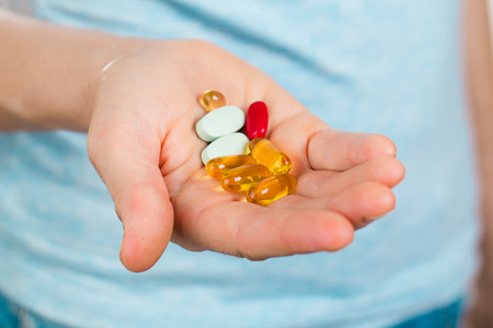 A hand holding many different types of pills or medicines.