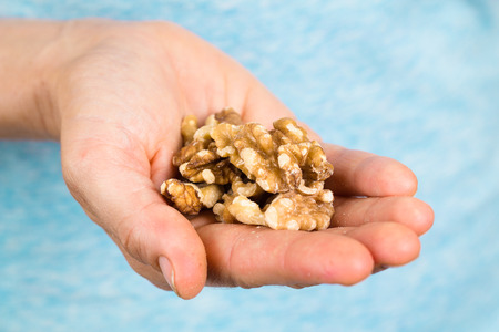Hand holding a heap of organic walnuts.