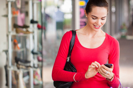 happy beautiful woman texting on a mobile or smart phone whilst out shopping. photo