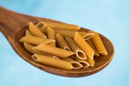 A hand holding a wooden spoon with wholemeal penne pasta