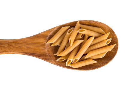 A wooden spoon with wholemeal penne pasta. Isolated on white.