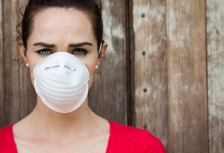 An unhappy woman wearing a face mask to deal with virus or pollution.