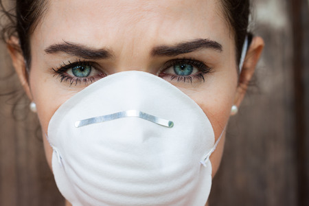 particulate: Close-up of an unhappy woman wearing a face mask to deal with virus or pollution. Stock Photo