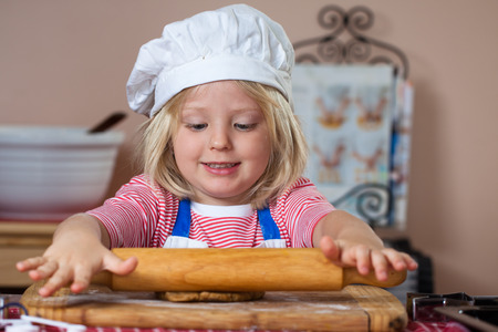 A cute young boy is baking and rolling out a gingerbread dough