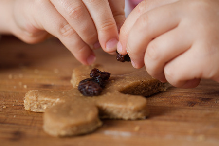 Close-up of a child putting raisins or sultanas on a gingerbread man