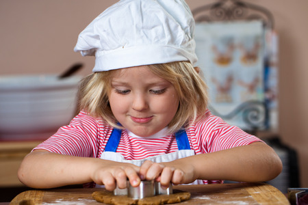 A cute young boy is baking and cutting out a gingerbread man Stock Photo