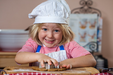 A cute smiling boy is baking and cutting out gingerbread shapes photo