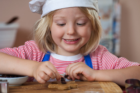 A cute young boy is baking and putting raisins on a gingerbread man  Stock Photo