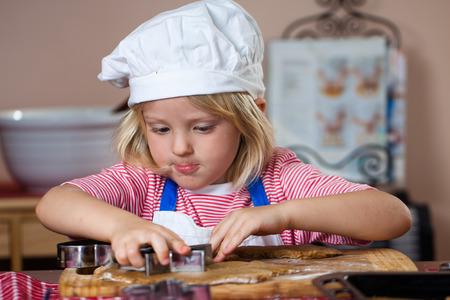 galleta de jengibre: Un niño lindo está concentrando mientras él está horneando galletas de jengibre Foto de archivo