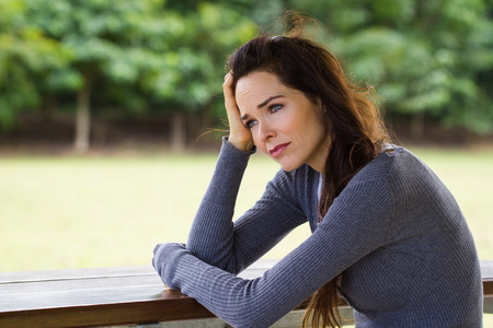A sad and depressed woman sitting down alone outdoors photo