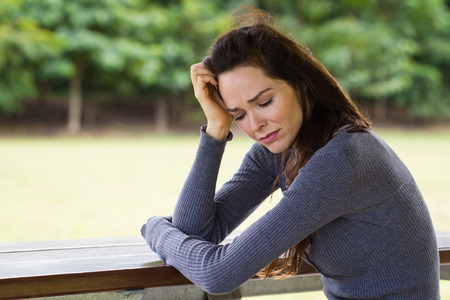 A sad and upset woman sitting down alone outdoors photo