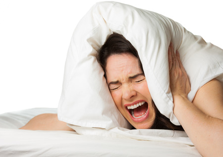 A frustrated tired woman screams and hides her head in her pillow because she cant sleep. Isolated on white.