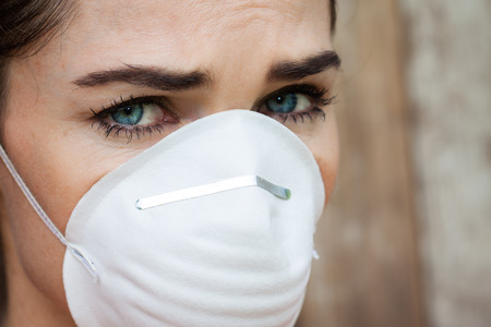 particulate: Close-up of an concerned woman wearing a face mask to protect herself from infection or air pollution.