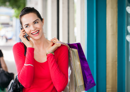 A beautiful woman out shopping is talking on her mobile phone. Stock Photo