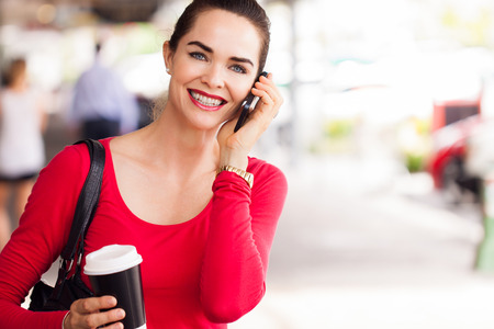 phone calls: A beautiful woman out shopping holding a cup of coffee and talking on the phone. Stock Photo
