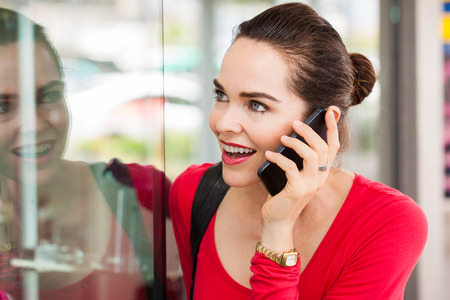 A beautiful happy woman is talking on the phone and looking in a shop window. Stock Photo