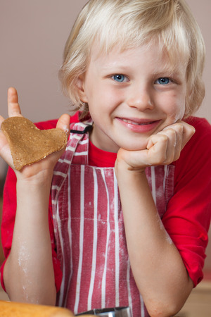 A cute young very proud boy is holding up a gingerbread love heart cookie he just baked Stock Photo
