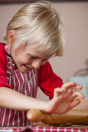 A cute young happy boy is baking and rolling out a gingerbread dough