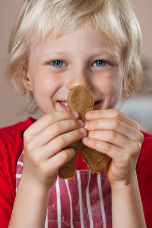 A close-up of a cute young very proud boy is holding up a gingerbread man he just baked