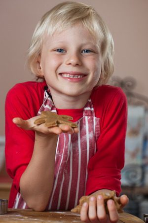 A cute smiling proud boy is holding up a gingerbread man he just baked photo