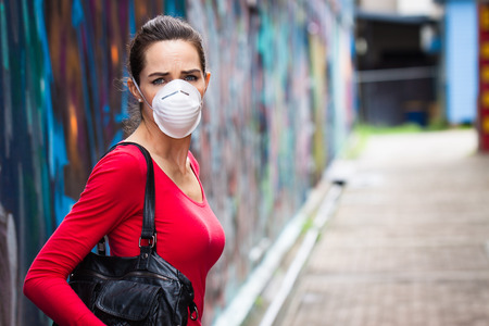 A woman on a street wearing a face mask looking upset photo