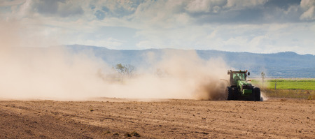Panorama of a tractor plowing very dry dusty  farm land in a drought