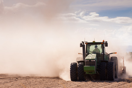 Close-up of a tractor plowing very dry and dusty farm land photo