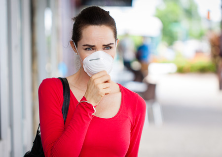 Een vrouw draagt een masker in de stad hoesten