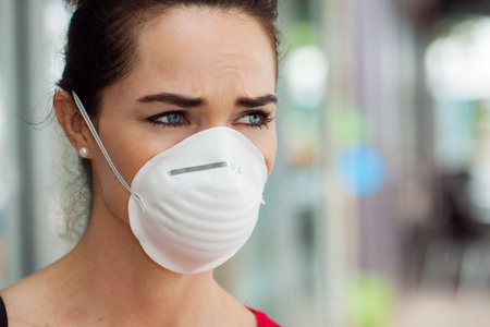 Close-up of a woman in the city wearing a face mask to protect herself from infection or air pollution  photo