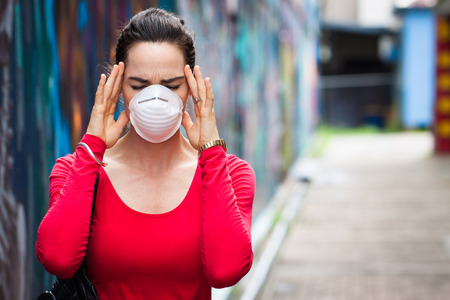 particulate: A woman with migraine or headache wearing a face mask