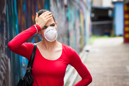 A woman with headache wearing a face mask in the city photo