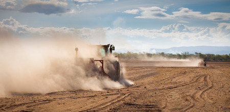 A tractor is plowing  very dry and dusty farm land in a drought