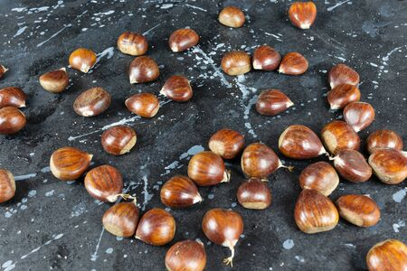 View of some raw chestnuts on a black background with gray moles